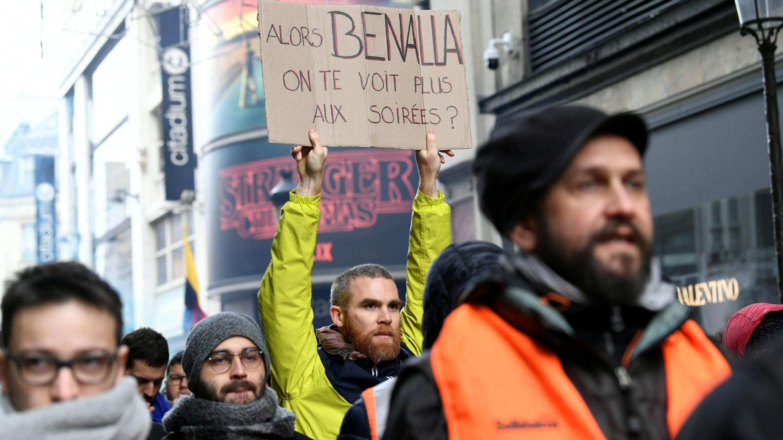 """Un hombre sostiene una pancarta que dice """"Entonces, Benalla, ya no te vemos en las fiestas"""" mientras asiste a una manifestación durante un día nacional de protesta del movimiento """"chalecos amarillos"""" en París, Francia, el 8 de diciembre de 2018."""