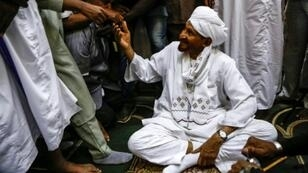 Sadiq al-Mahdi, Sudan's ex-prime minister and leader of the opposition Umma Party, is greeted by supporters in a mosque in the capital Khartoum's twin city of Omdurman on December 19, 2018 after his return from exile