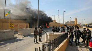 Iraqi security forces at the entrance of the U.S. Embassy in Baghdad on January 1, 2020, as smoke billows following a demonstration.