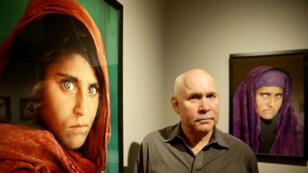 Le photographe Steve McCurry pose devant sa célèbre photo de Sharbat Gula, lors d'une exposition à Hambourg, en juin 2013..