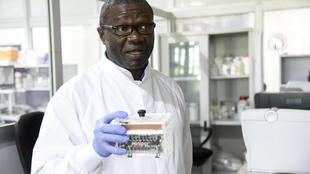 Molecular biologist Christian Happi, head of the ACEGID genomics lab, holds a thermal cycler, which amplifies genetic segments of the virus