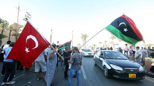 Tripoli residents in June 2020 wave the flags of Libya and Turkey, which has accused the European Union of bias in trying to stop its shipments of weapons to the country's internationally recognized government