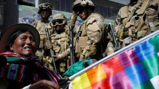 Un grupo de militares observa a una mujer que porta la bandera indígena Whipala durante las protestas en La Paz, Bolivia, el 15 de noviembre de 2019.