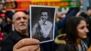 رجل يحمل صورة لصلاح الدين دميرتاش أثناء تجمع لأنصار زعيم أكبر حزب مناصر لأكراد تركيا أمام محكمة في إسطنبول في 12 ك2/يناير 2018