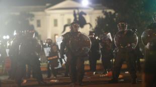 Des manifestants qui dénoncent les violences policières et des policiers se sont face à quelques rues de la Maison Blanche à Washington, le 31 mai 2020.