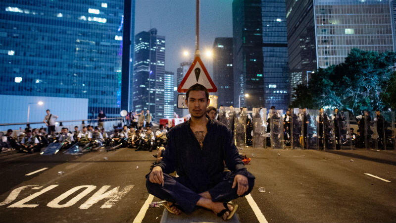 Philip Fong, AFP | A protester sits in the middle of Hong Kong's Harcourt Road, joining the thousands of people blocking the city's main arteries in protest of the proposed law