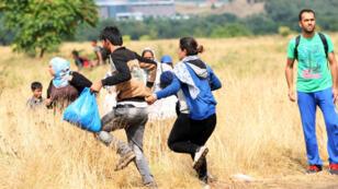 Des migrants partent en courant à la frontière avec la Grèce, près de la ville macédonienne d'Idomeni, le 22 août 2015.
