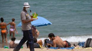 Un vendedor sirve bebidas a los bañistas el 9 de julio de 2020 en la playa de la Barceloneta, en Barcelona