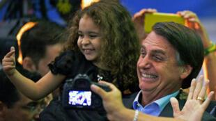 El candidato a las elecciones presidenciales de Brasil, Jair Bolsonaro, posa con una niña en el lanzamiento de su campaña en Río de Janeiro, Brasil, el 22 de julio de 2018.