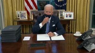 الرئيس الأمريكي الجديد جو بايدن يوقع في المكتب البيضاوي بالبيت الأبيض إثر أدائه اليمين الدستورية سلسلة أوامر تنفيذية في 20 ك2/يناير 2021.
