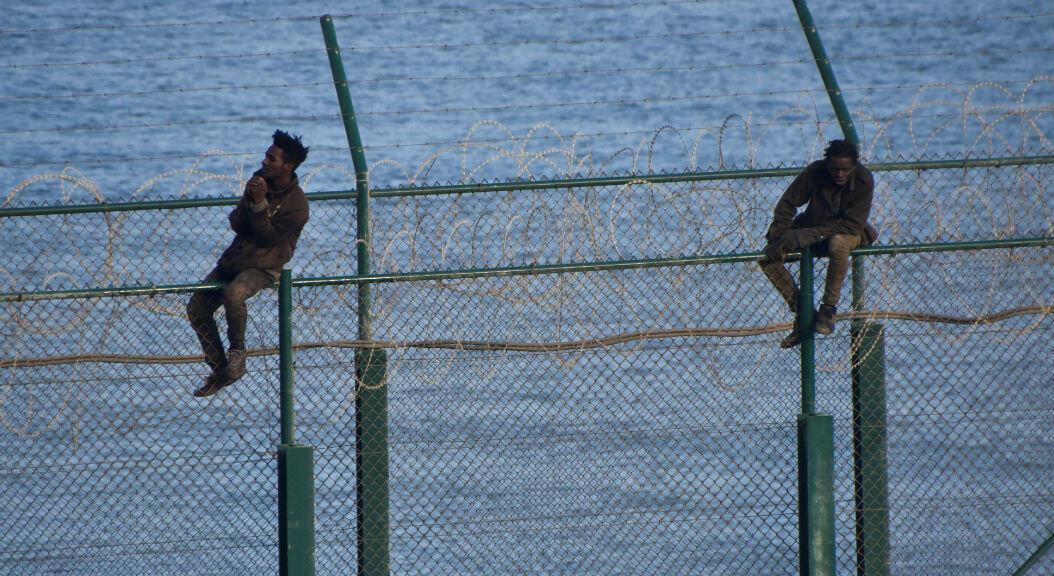 Hombres africanos intentan cruzar una valla en el enclave de Ceuta, España, frontera con en el norte de África, el 30 de agosto de 2019, después de que otro grupo de alrededor de 150 migrantes pasara a la fuerza.