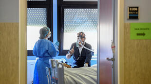 A medical worker wearing a protective mask and suit speaks with a patient suffering from coronavirus in an intensive care unit at the Oglio Po hospital in Cremona, Italy, March 19, 2020.