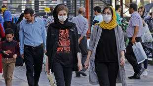 Iranians, some wearing face masks, walk in the capital Tehran on June 3, 2020. The spread of the novel coronavirus has accelerated again this month in Iran, with over 3,000 confirmed new cases for a third consecutive day.