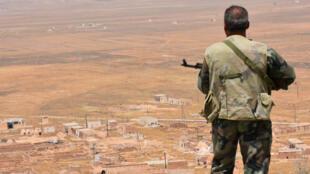 Un soldat syrien photographié sur une colline surplombant Khanasser, près d'Alep, le 2 juillet 2017