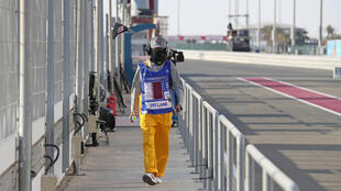Un mecánico camina por el 'pit lane' del circuito de Losail tras la cancelación del Gran Premio de Catar de MotoGP, el 6 de marzo de 2020 a las afueras de Doha