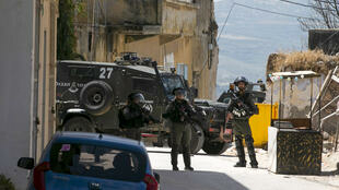 جنود إسرائيليون قرب عربة عسكرية