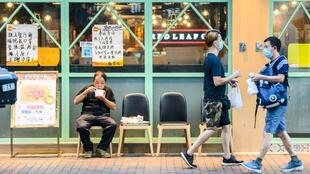 A man eats a takeaway meal outside a restaurant in Sham Shui Po, Hong Kong, after the dine-in ban was introduced