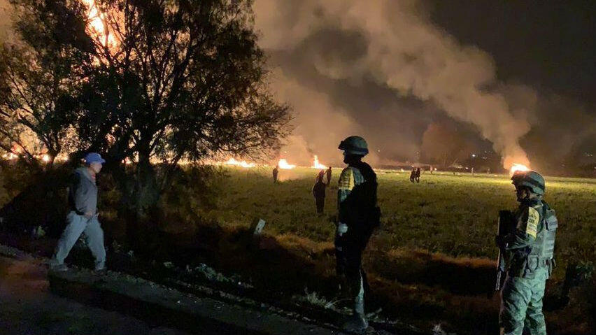 Soldatos observan las llamas envolviendo el área después de que explotara una tubería de combustible averiada, en Tlahuelilpan, Hidalgo, México, el 18 de enero de 2019.