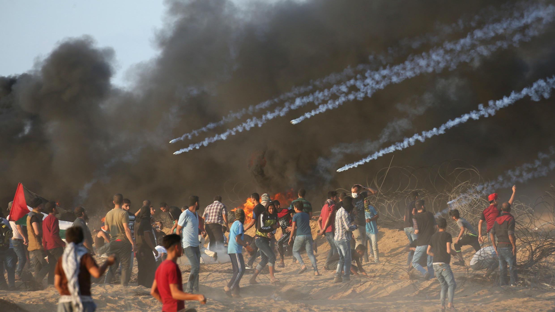 Bombas de gas lacrimógeno son disparados por las tropas israelíes hacia los manifestantes palestinos durante una protesta que pide levantar el bloqueo israelí en Gaza y exigir el derecho a regresar a su país de origen, en la valla fronteriza entre Israel y Gaza en el sur de la Franja de Gaza, el 12 de octubre de 2018.