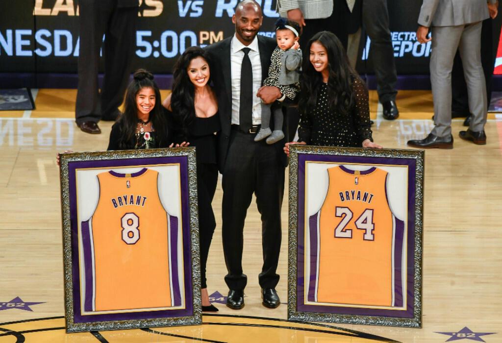 Kobe Bryant pose en famille sur le parquet des Lakers, avec ses deux maillots, le numéro 8 porté jusqu'en 2006, avant d'adopter le 24 pour la suite de sa carrière.