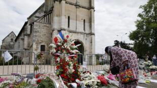 Des passants déposant des fleurs devant l'église de Saint-Étienne-du-Rouvray, le 29 juillet 2016, trois jours après l'assassinat du père Hamel.