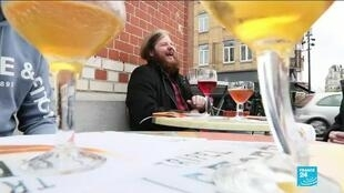 A man laughs over beer with friends on a newly reopened Brussels terrace after a long wait due to the Covid-19 pandemic.