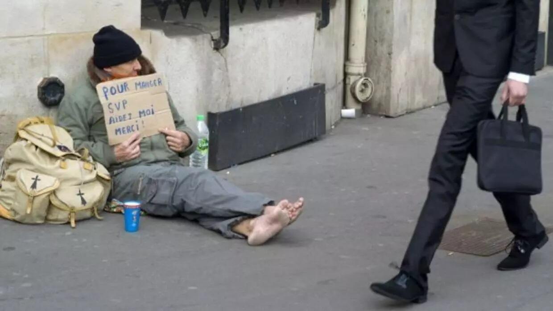 فقير يتسول على الرصيف.