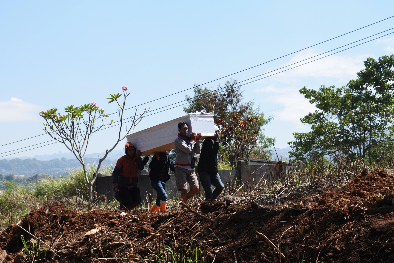 Поскольку число инфекций продолжает расти, кладбищенские работники несут гроб жертвы вируса короны-19 в Индонезии.