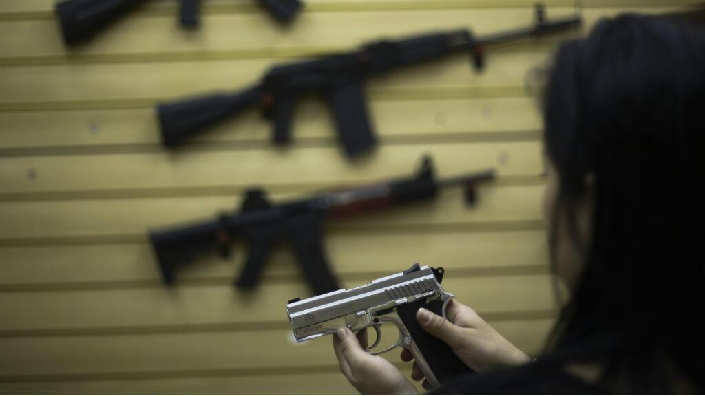 Foto de archivo de una mujer que maneja una pistola en una tienda de armas en Sao Caetano do Sul, en Sao Paulo, Brasil, el 30 de octubre de 2015.