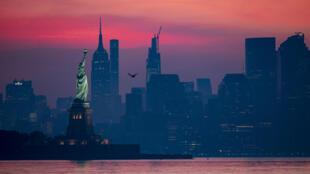 تمثال الحرية وخلفه طرف من حي مانهاتن بمدينة نويورك فجر 19 تموز/يوليو 2020