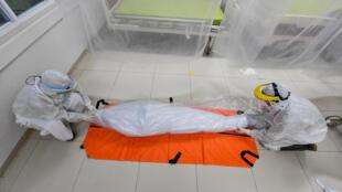 نقل جثمان مصاب بكوفيد-19 منن قبل عمال مكتب دفن في مستشفى في بوغور، في إندونيسيا في 9 أيلول/سبتمبر 2020