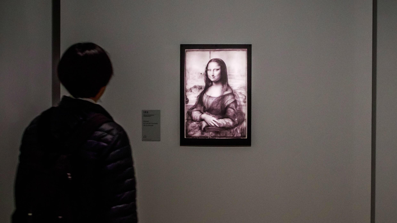 Un visitante mira una reflectografía infrarroja de la pintura 'Mona Lisa', del artista renacentista italiano Leonardo Da Vinci, durante una exposición en el Museo del Louvre en París, Francia, el 22 de octubre de 2019.