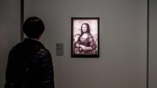 """Un visiteur regarde une réflectographie infrarouge du tableau """"Mona Lisa"""" de l'artiste Leonardo Da Vinci, lors d'une exposition au Musée du Louvre à Paris, France, le 22 octobre 2019."""