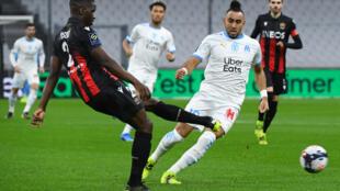 Le défenseur de Nice Stanley Nsoki (g) devant le milieu de l'OM Dimitri Payet, le 17 février 2021 à Marseille