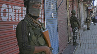 Indian paramilitary troops stand guard in front of closed shops in Srinagar