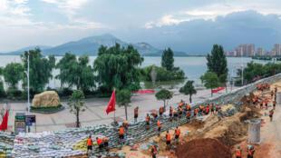 صورة مؤرخة في 13 تموز/يوليو 2020 تظهر جنودا صينيين فيما يحاولون التصدي للفيضانات حول بحيرة بويانغ في جيانغشتي
