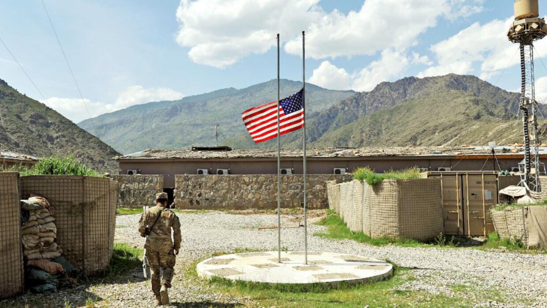 Dans cette photo d'archive prise le 18 avril 2013, un soldat de l'armée américaine passe devant le drapeau américain en berne à la base avancée Honaker Miracle dans le district de Watahpur dans la province de Kunar.