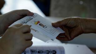 Un votante obtiene una papeleta durante la elección presidencial en una mesa electoral en San José, Costa Rica , el 1 de abril de 2018.