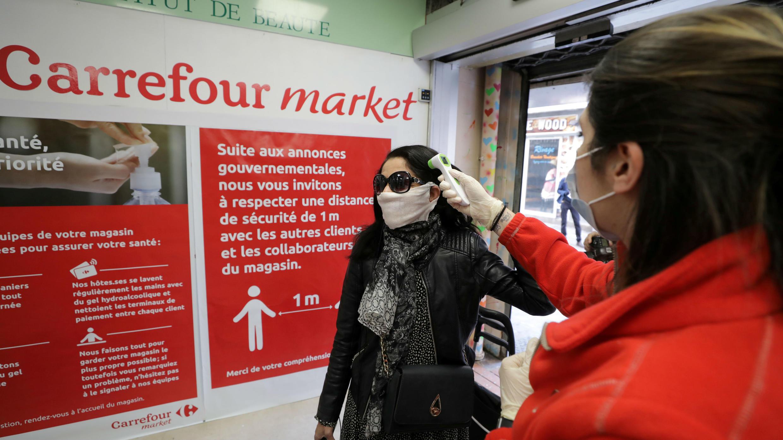 Una empleada, que usa una máscara facial, verifica la temperatura de una clienta antes de que ingrese al mercado Carrefour en Cannes, mientras la propagación de la enfermedad del nuevo coronavirus continúa en Francia, el 8 de abril de 2020.