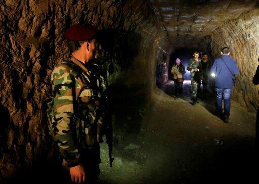 جنود سوريون وصحافيون داخل نفق سبق أن استخدمته فصائل المعارضة في حي جوبر في الغوطة الشرقية خلال جولة في الثاني من نيسان/أبريل 2018