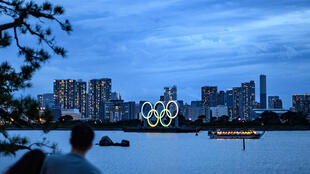 The Olympic Rings are displayed in Tokyo near a seaside park. Many questions remain unanswered with a year to go till the delayed Games