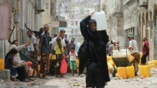 يمنيون يملؤون أوعية بالماء في عدن في 19 تموز/ يوليو 2015