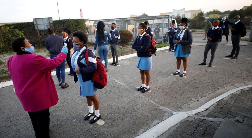 Archivo-Una profesora toma la temperatura a un grupo de estudiantes, tras el retorno a clases, en Cape Town, Sudáfrica, el 8 de junio de 2020.