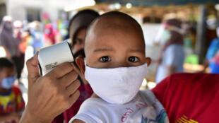 Vérification de la température d'un enfant, masqué, en Thaïlande dans la cadre de la prévention du Covid-19, le 17 avril 2020
