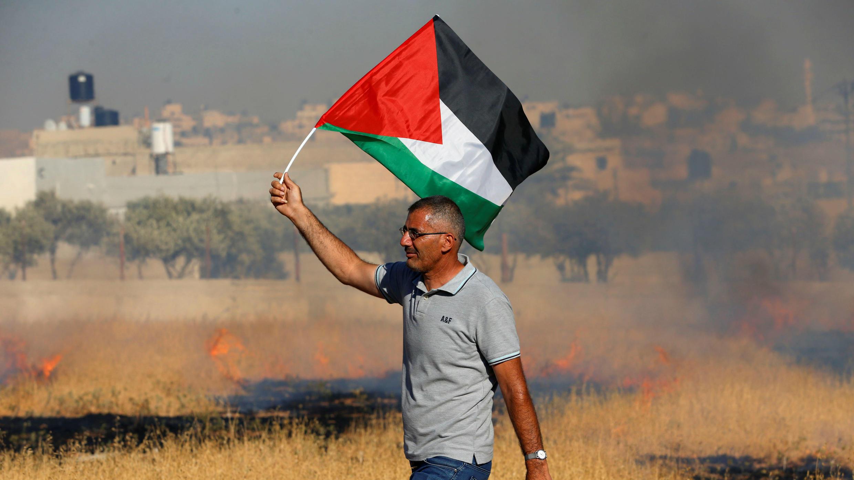 Un manifestante sostiene una bandera palestina durante una protesta contra los planes israelíes de demoler viviendas palestinas en la aldea de Sur Baher, que se encuentra a ambos lados de la barrera en Jerusalén Este y en la Cisjordania ocupada por Israel el 20 de julio