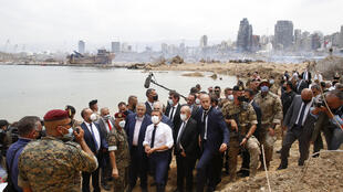 French Foreign Minister Jean-Yves Le Drian (C,R) accompanies French President Emmanuel Macron (C) on a visit to the site of the devastating explosion at the port of Beirut, Lebanon, on August 6, 2020.