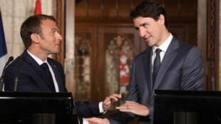 """El primer ministro canadiense Justin Trudeau (der) y el presidente  francés Emmanuel Macron (izq) se saludan tras una conferencia conjunta en la sede del Parlamento canadiense en Ottawa el 7 de junio.  Ambos expresaron su apoyo al """"multilateralismo"""" antes de la cumbre del G-7 donde las políticas agresivas de Donald Trump prometen poner los pelos de puntas a los participantes."""