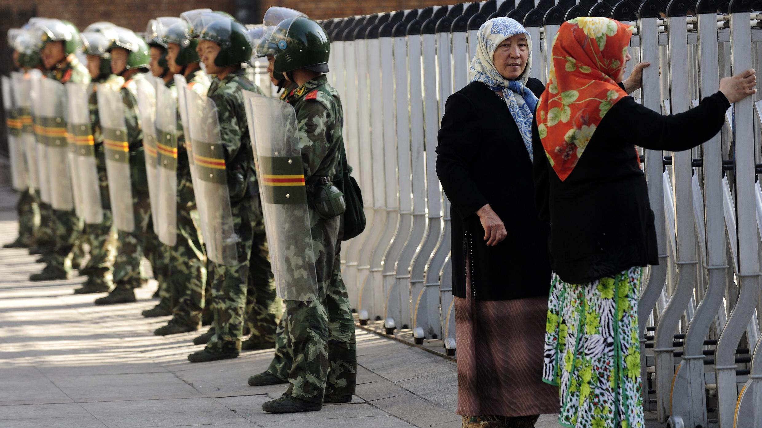 An ethnic Uighur woman looks through a security fence at the Grand Bazaar as Chinese soldiers watch in Urumqi, in China's far western region of Xinjiang on 9 July 2009.