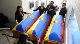 Personal funerario extiende banderas ecuatorianas sobre los ataúdes de los dos periodistas y su conductor que fueron asesinados por disidentes guerrilleros en la frontera entre Colombia y Ecuador. 26 de junio, 2018.