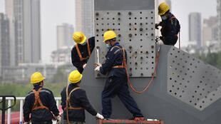 Workers wearing protective masks work on a bridge in Wuhan, China, on March 24, 2020, after the construction works resumed following the lockdown to curb the spread of the coronavirus.